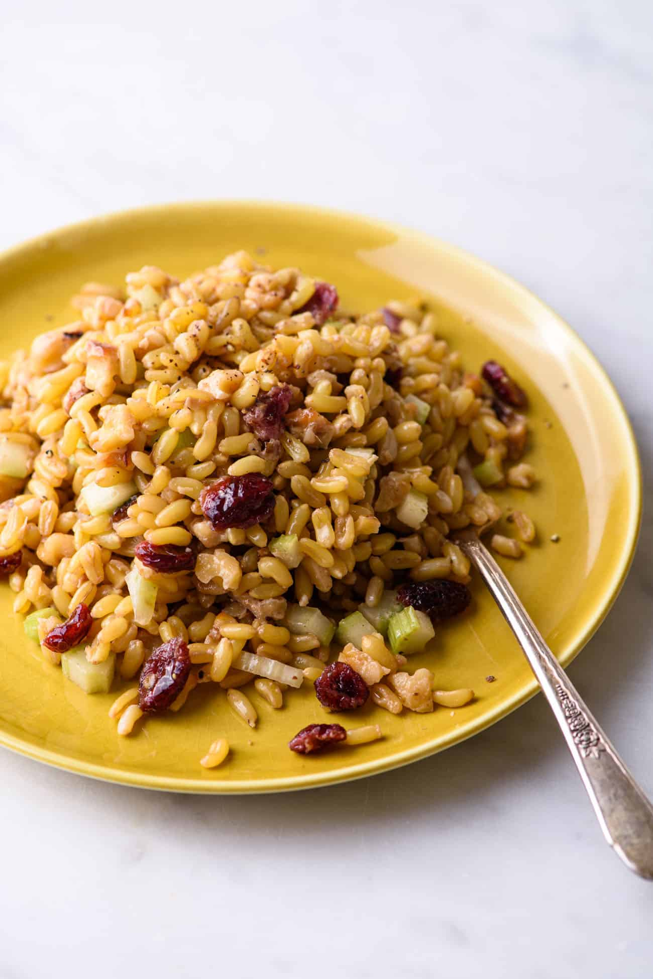 Close-up of wheatberry salad on a yellow plate with a fork