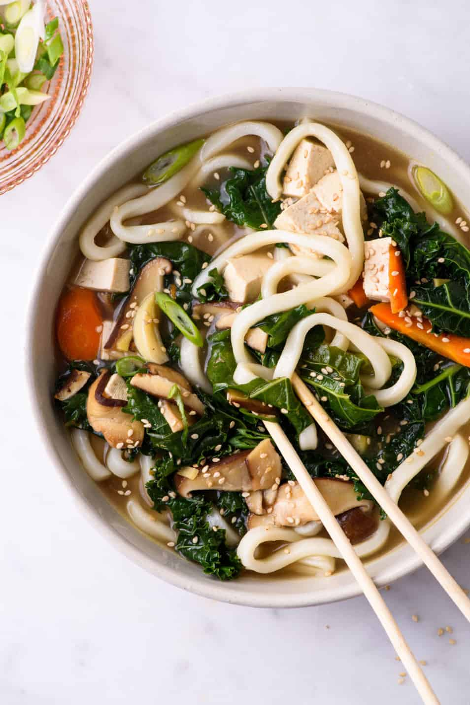 Close-up of bowl of sick day soup with noodles, tofu, kale and shiitakes
