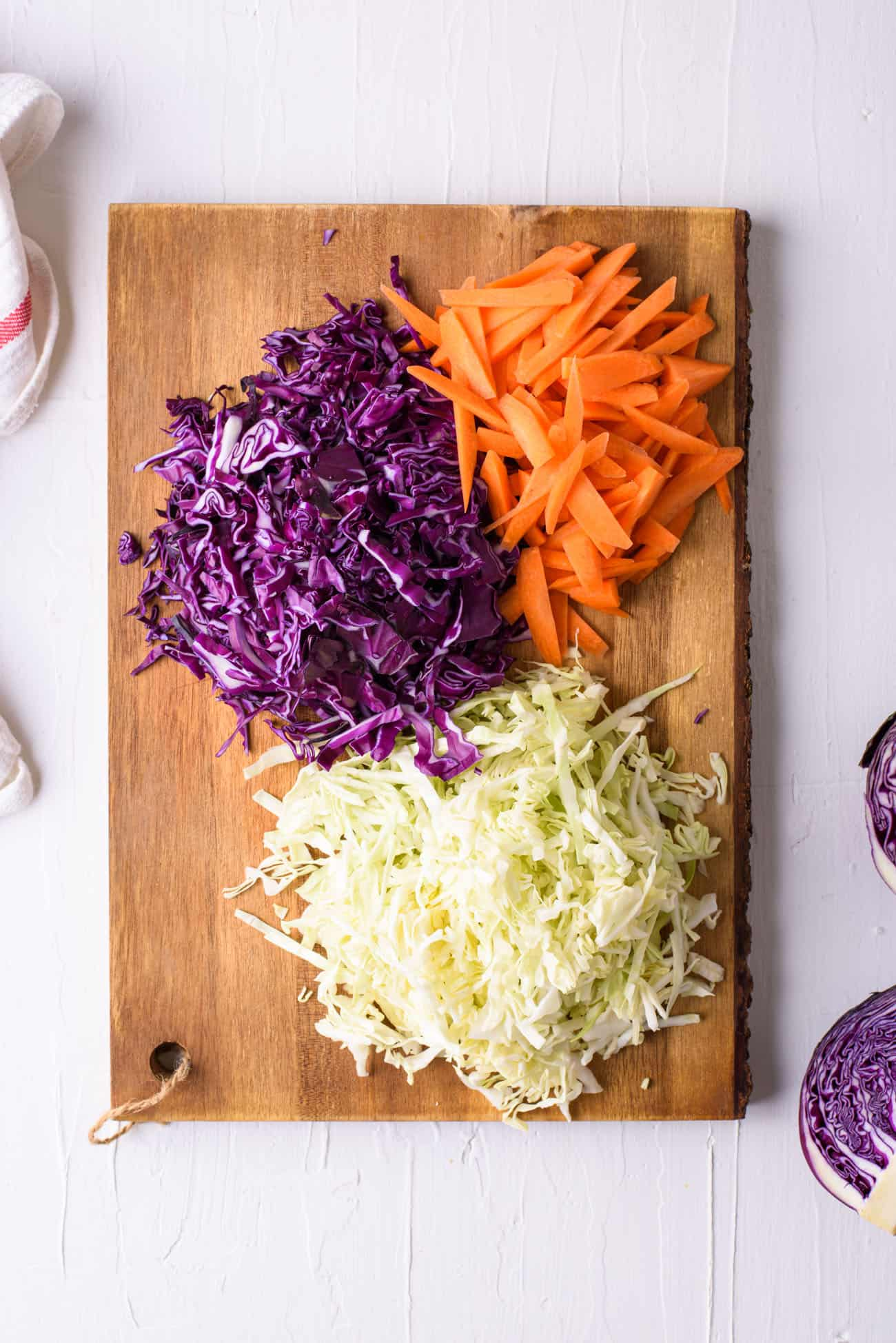 Shredded green and purple cabbage, and carrot matchsticks, on a wooden cutting board on a white table