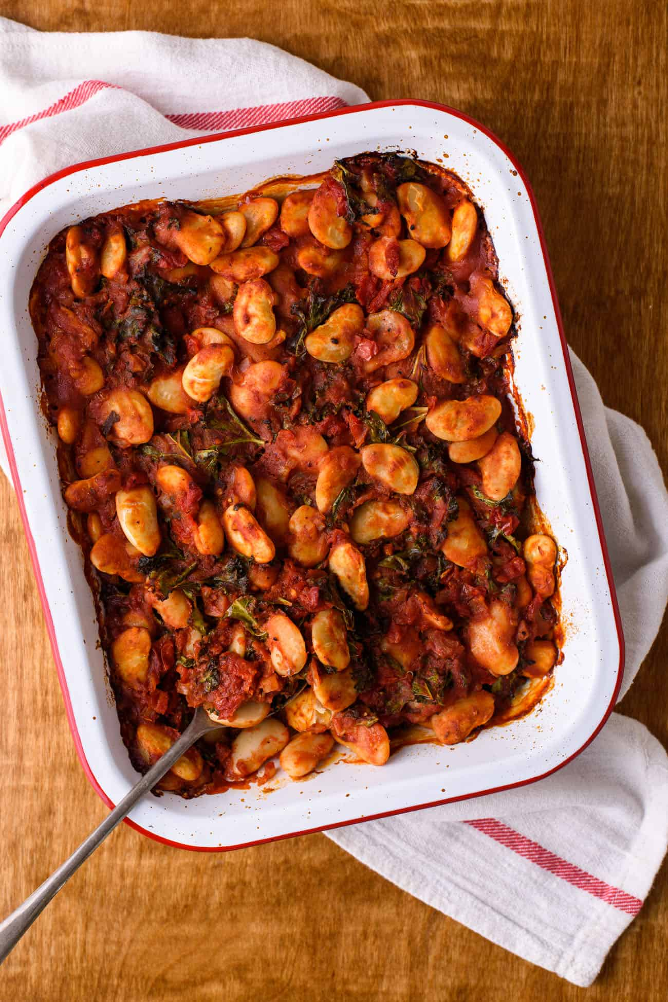 Greek baked beans in an enamel baking dish