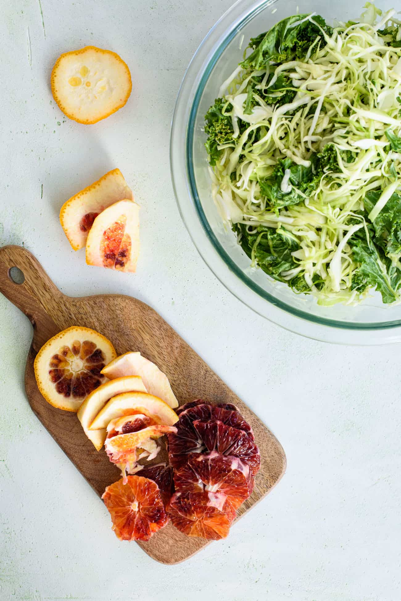 Peeled blood orange on a small cutting board next to a bowl of cabbage and kale