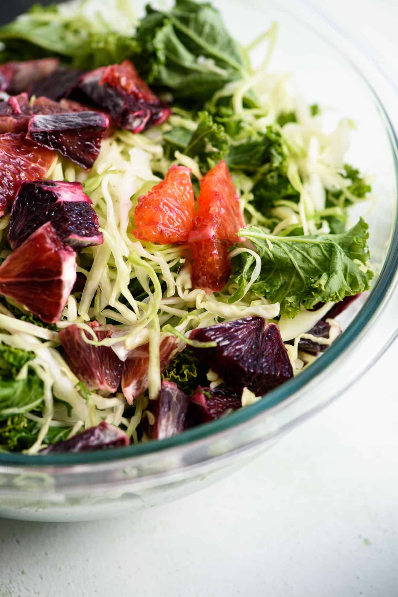 Close-up of Pyrex bowl with shredded cabbage, kale, and citrus