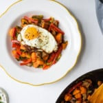 Sweet potato breakfast hash in a white bowl topped with a fried egg