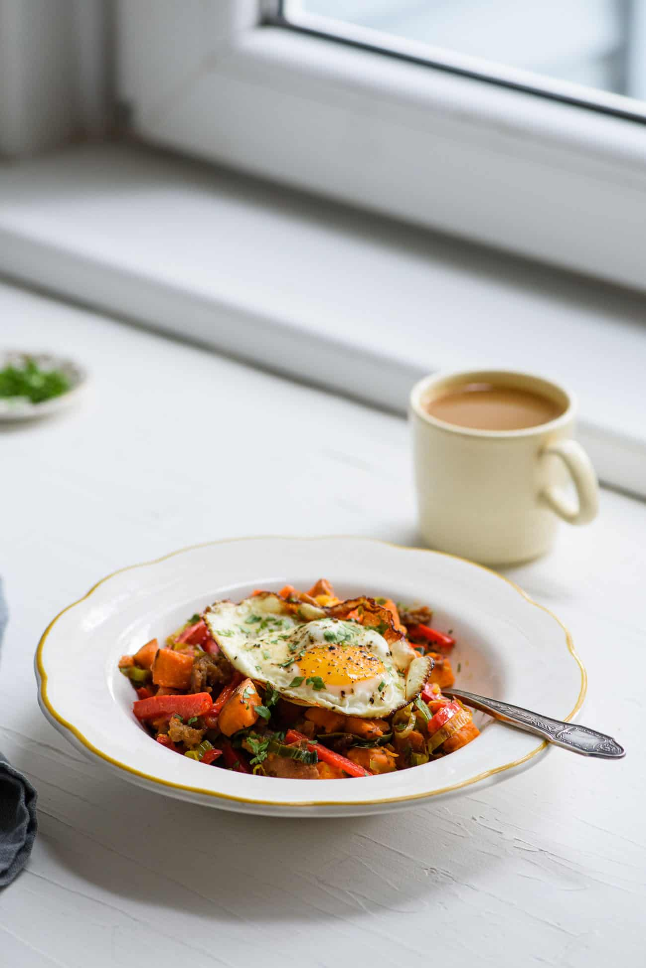 Sweet potato breakfast hash in a white bowl next to a cup of coffee