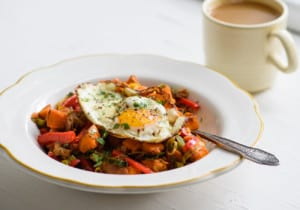 Sweet potato breakfast hash with a fried egg in a white bowl next to a cup of coffee