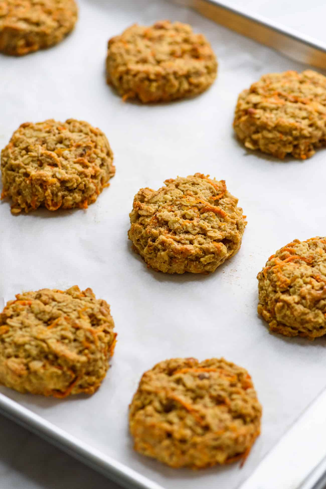 Vegan carrot oatmeal cookies on a baking sheet with parchment paper