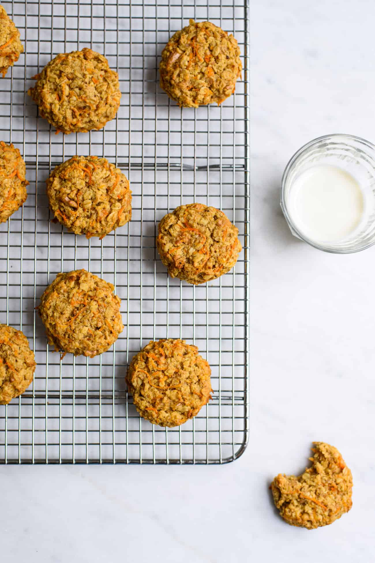 Carrot oatmeal cookies on a cooling rack next to a glass of milk