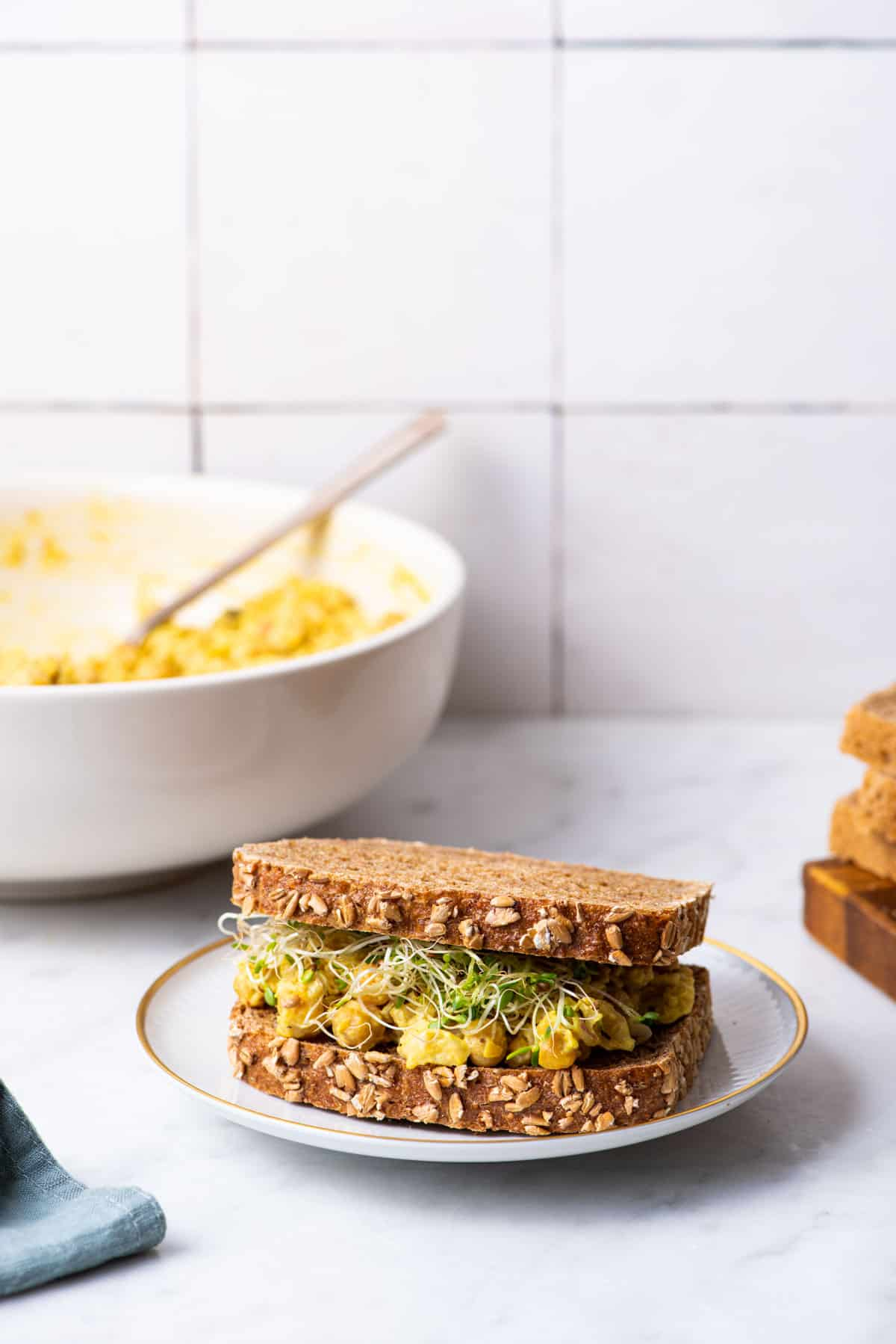 Curried chickpea salad sandwich on whole wheat bread with sprouts on a marble counter.