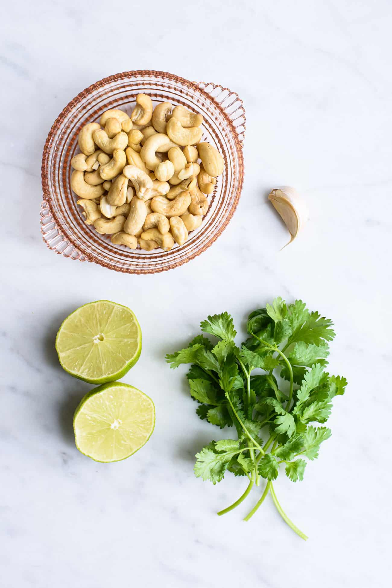 Cashews, lime, cilantro and garlic laid out on a marble table