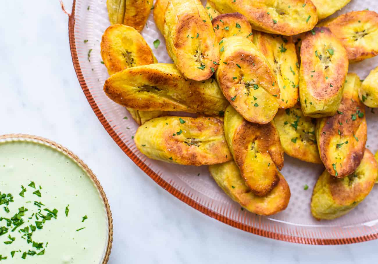 Pan-fried plantains on a pink glass platter next to cilantro-lime cashew cream