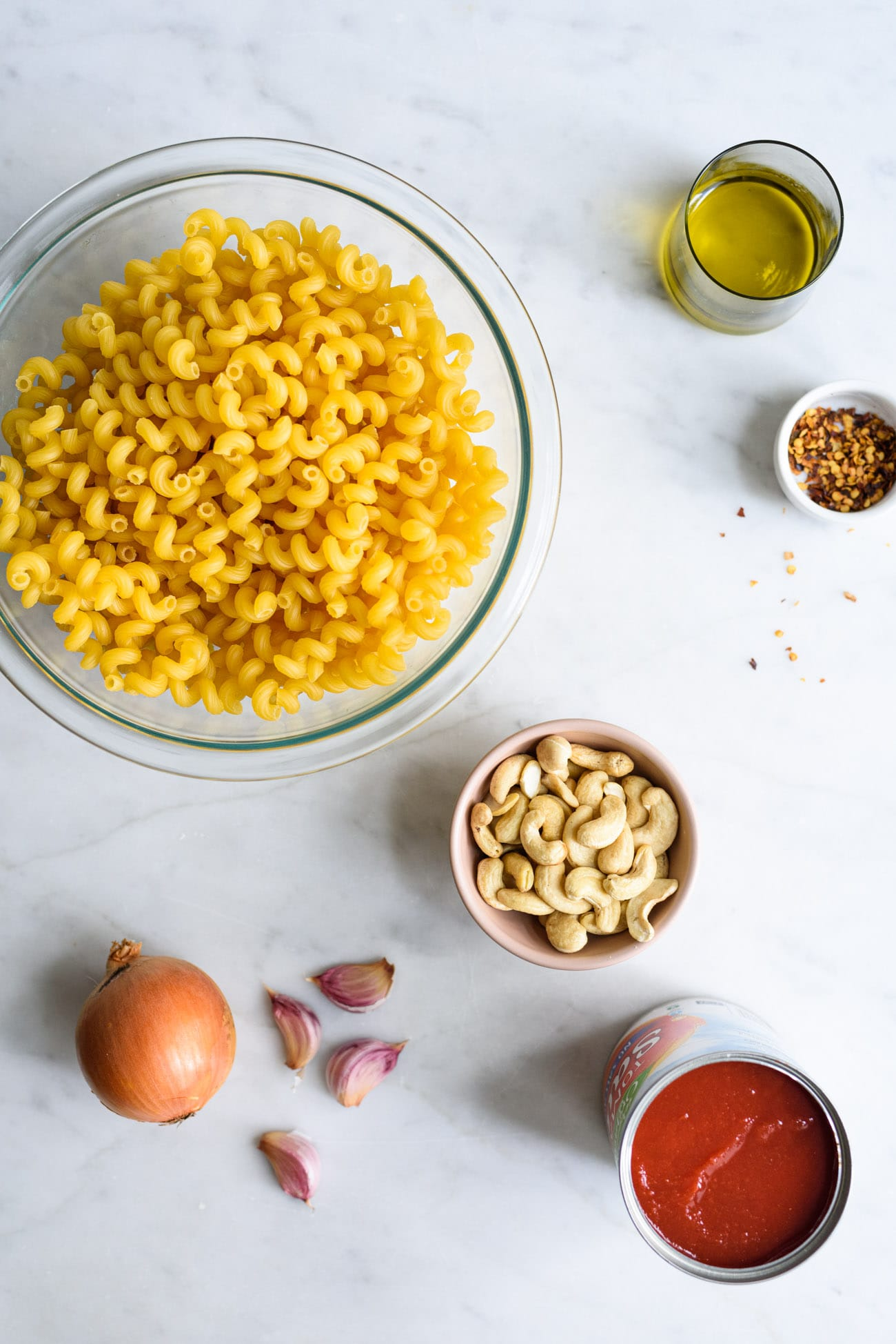 Ingredients to make vegan creamy tomato pasta laid out on a marble counter: cavatappi, cashews, canned tomato sauce, onion, and garlic