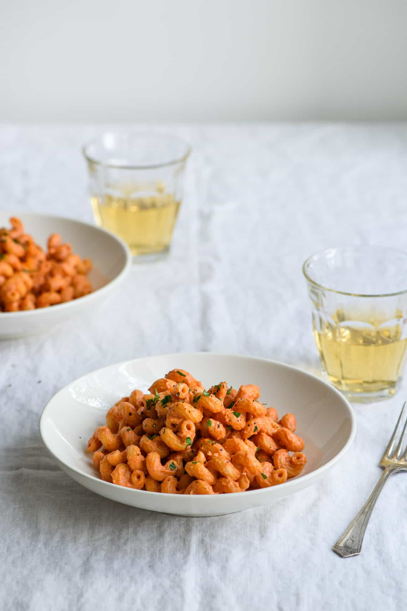 Two bowls of creamy tomato pasta with vegan vodka sauce on a white tablecloth next to glasses of white wine