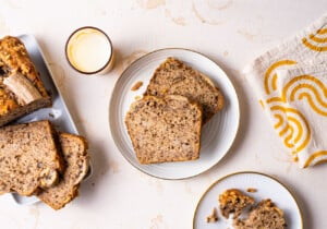Slices of vegan banana bread on a cooling rack alongside cups of coffee on a marble table