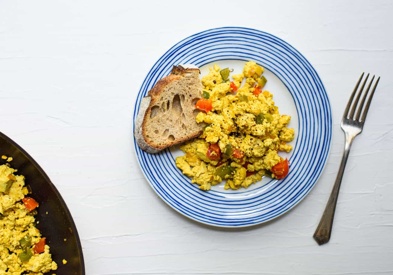 Mexican tofu scramble on a blue-rimmed plate with a piece of sourdough toast
