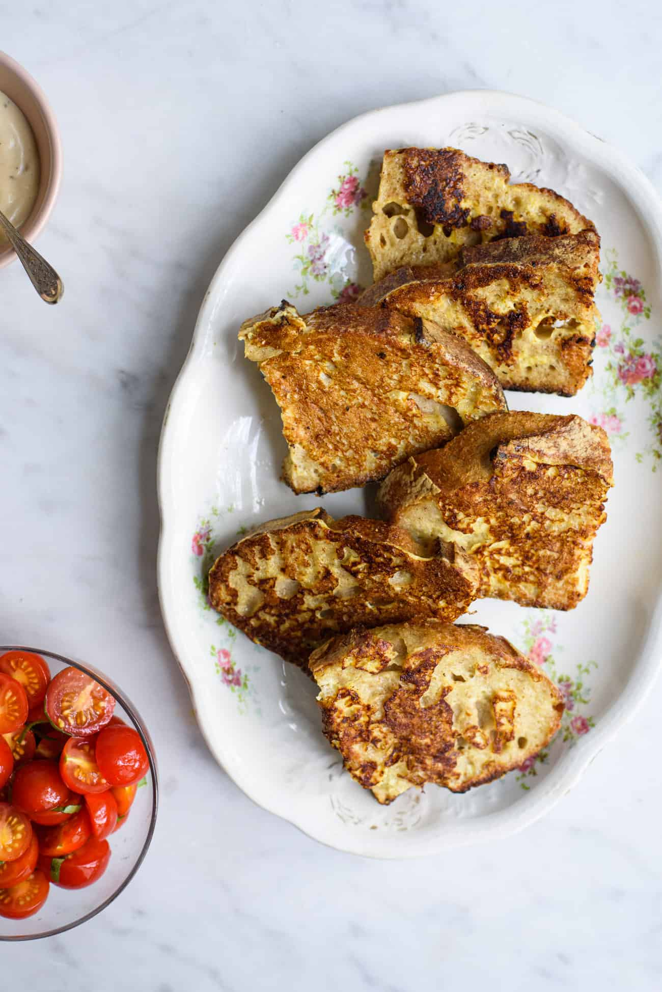 Slices of savory French toast overlapping on a vintage floral platter