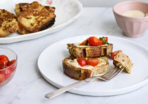 Savory French toast with tomato-basil salad on a white plate