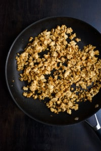Cooked tempeh in a skillet on a black table