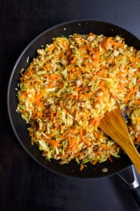 Cooked cabbage and carrots in a skillet on a black table