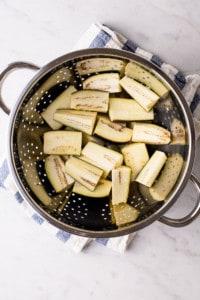 Zoute aubergine in een vergiet op een gestreepte keukendoek