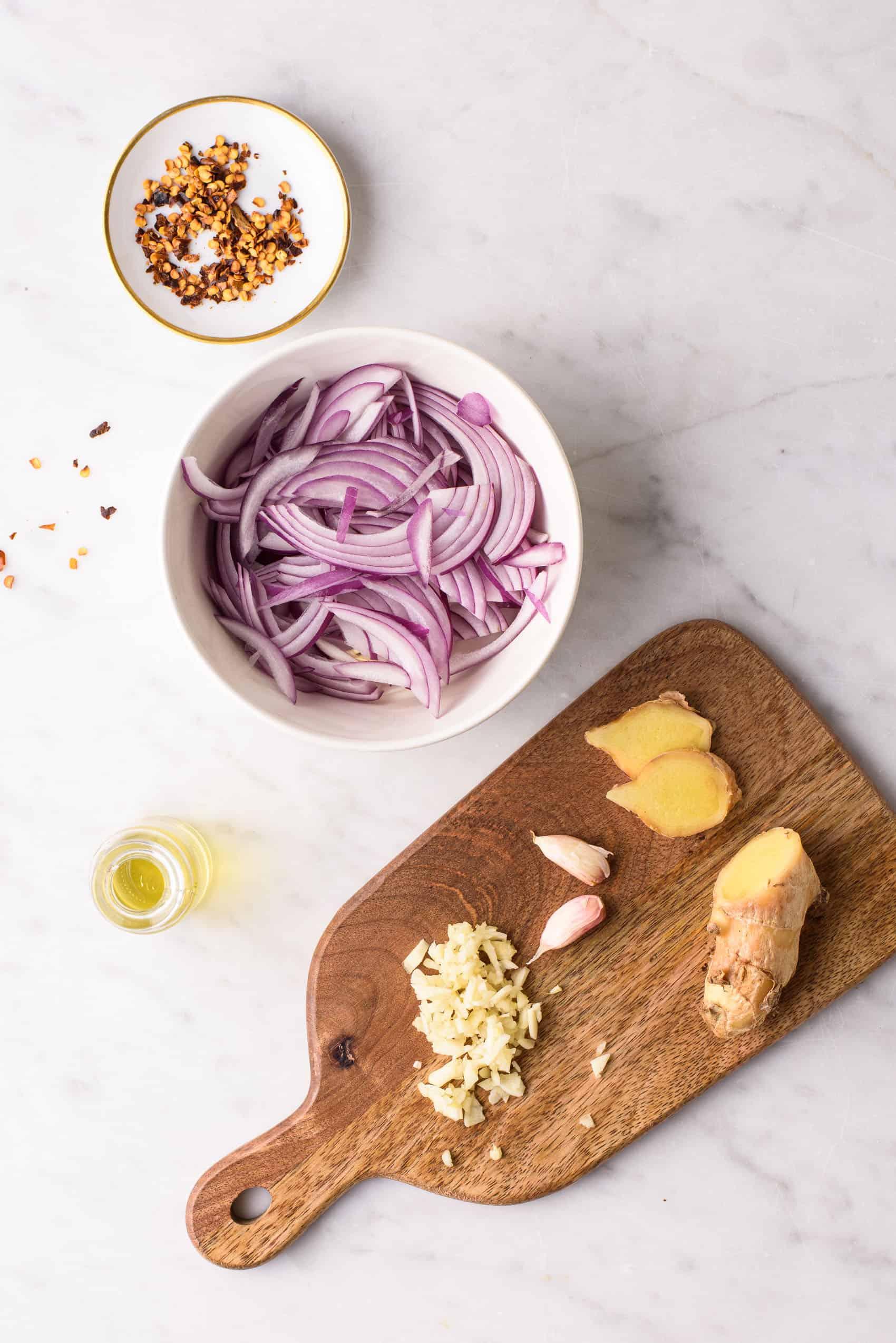 Pepervlokken, gesnipperde rode ui, en gehakte knoflook en gember op een snijplank, alles klaargezet op een marmeren tafel