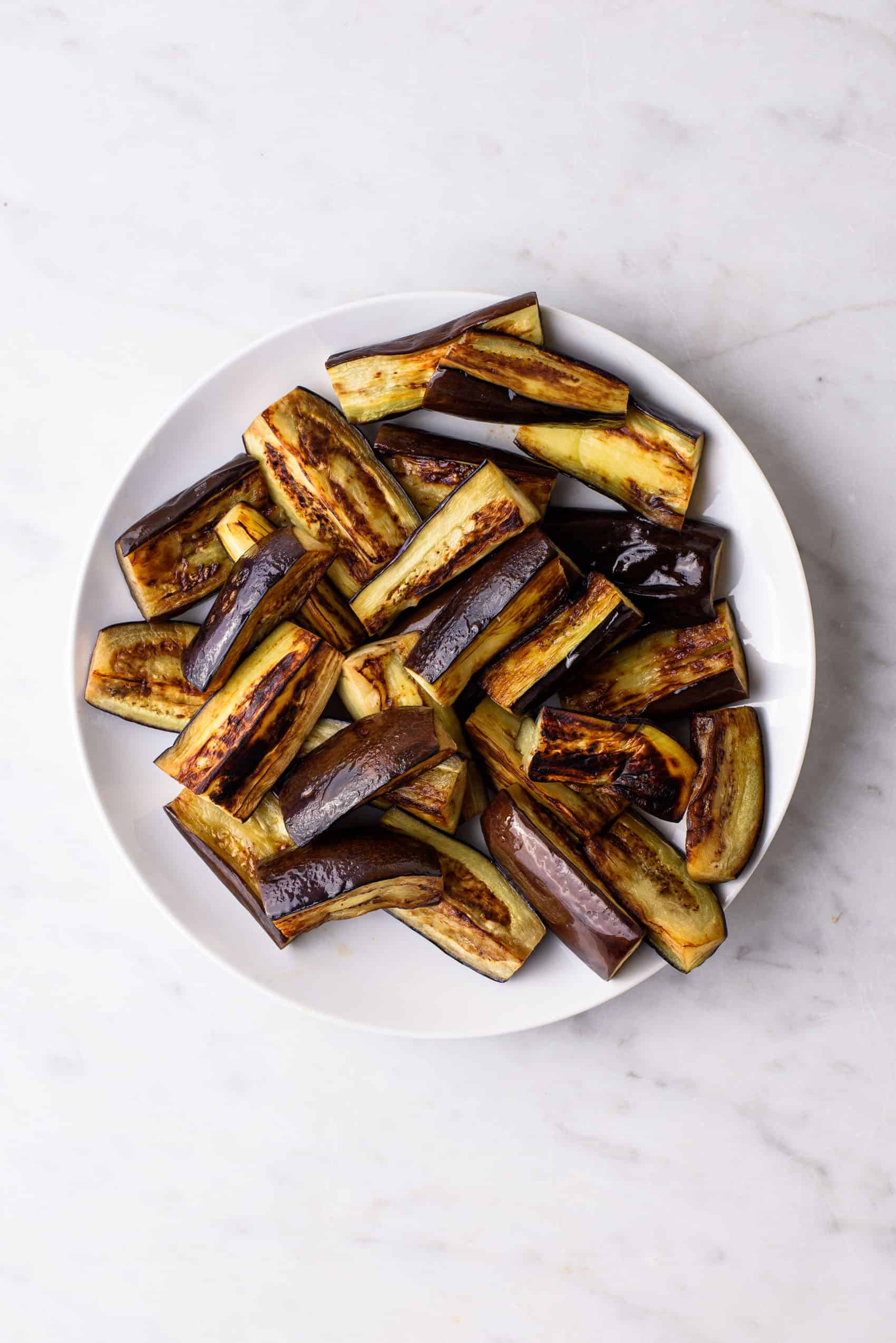 Caramelized pan-fried eggplant on a white plate