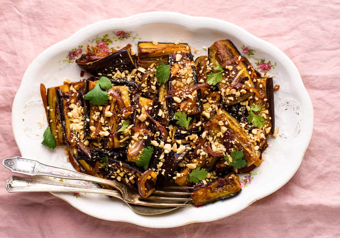 Soy-glazed pan-fried eggplant sprinkled with crushed peanuts and cilantro on a vintage oval platter on a pink tablecloth