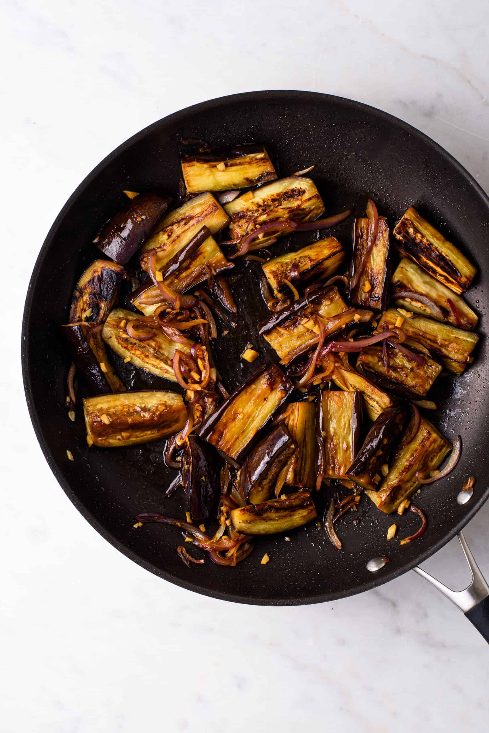 Soy-glazed eggplant in a non-stick skillet on a marble table