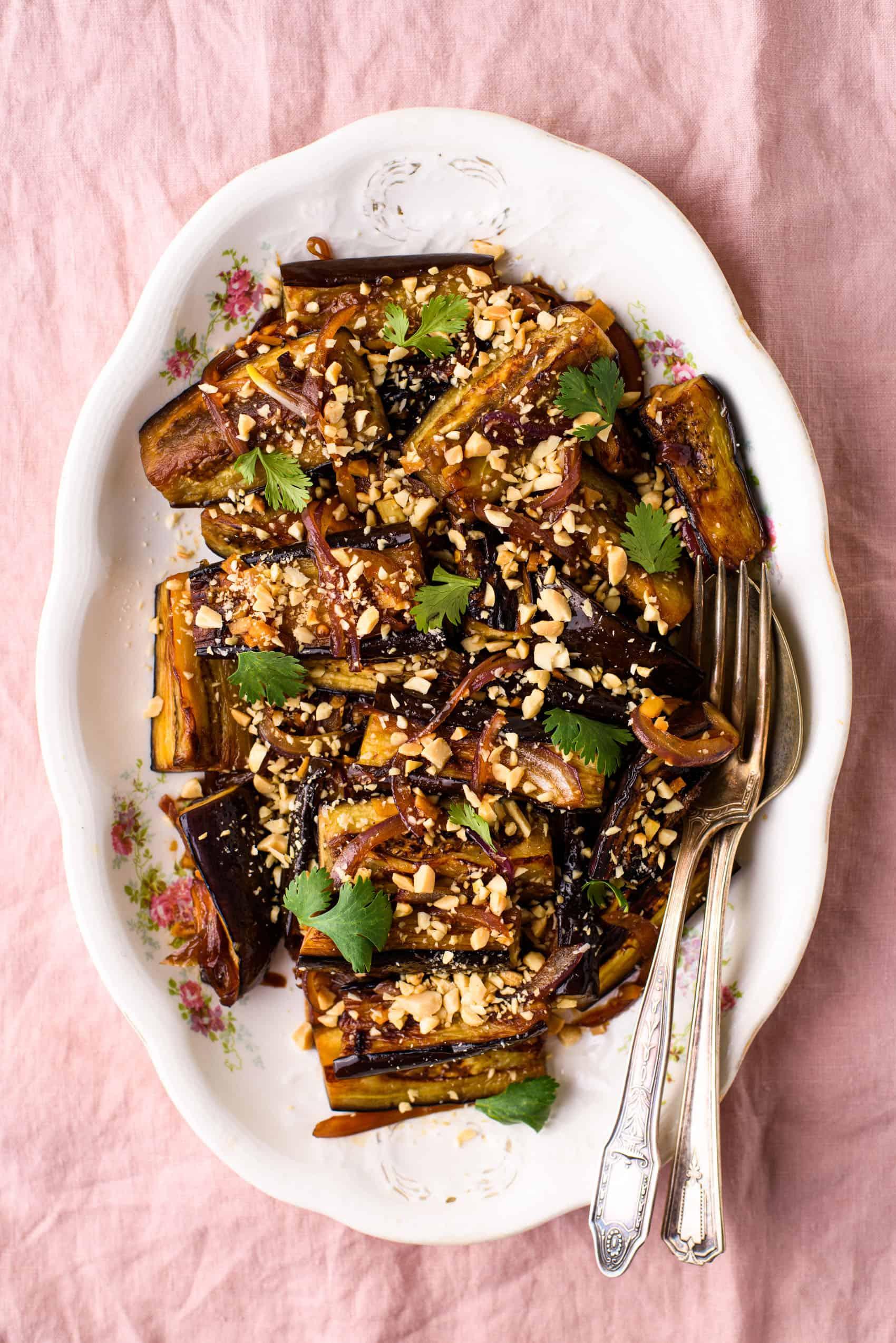 Geglazuurde, in de pan gebakken aubergine bestrooid met gemalen pinda's en koriander op een vintage, ovale schaal op een roze tafelkleed
