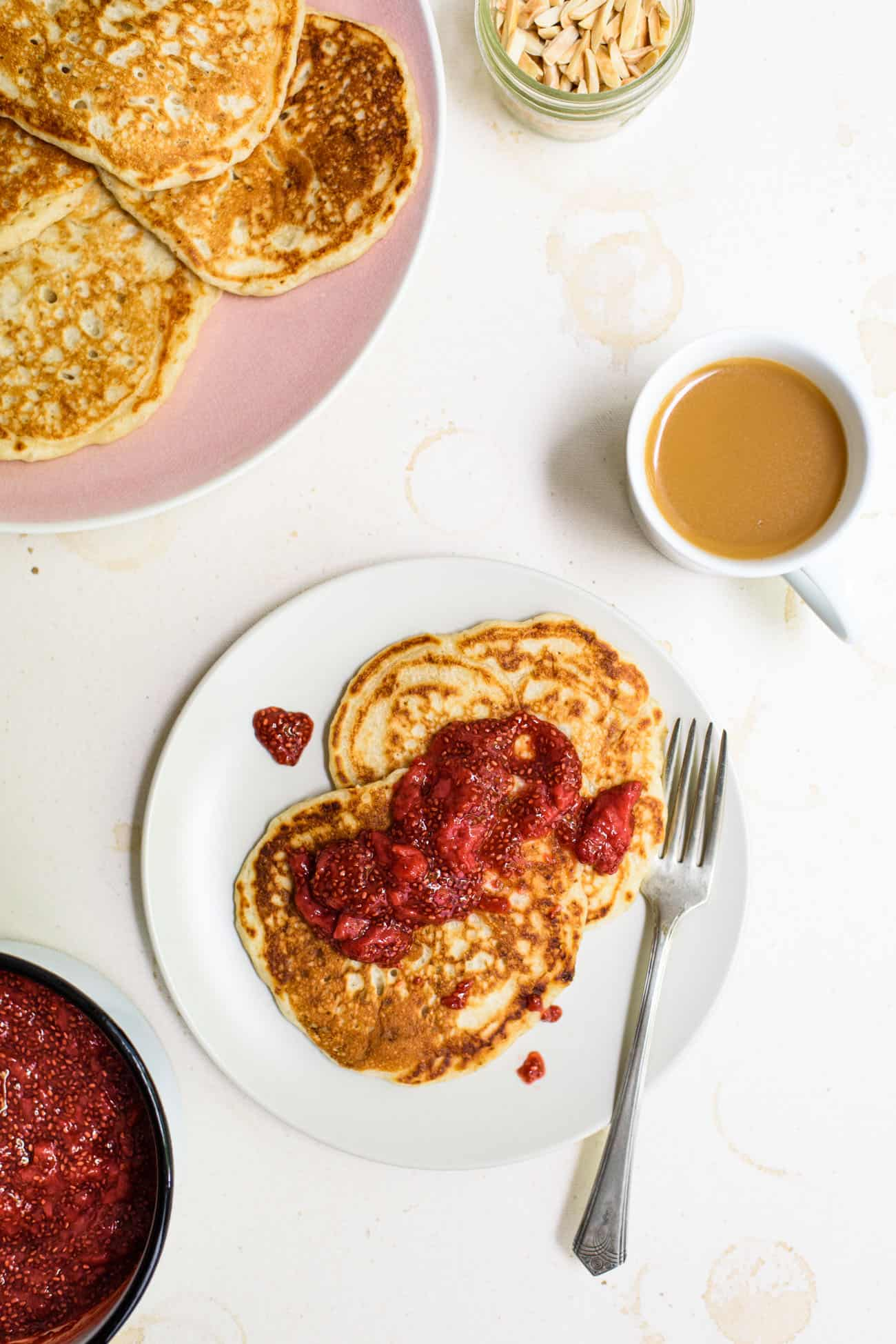 Two sourdough discard pancakes on a white plate, dolloped with strawberry chia jam, next to a cup of coffee