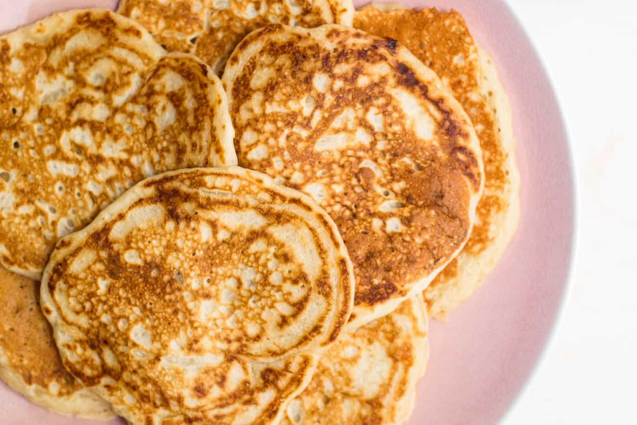 Sourdough discard pancakes on a pink platter