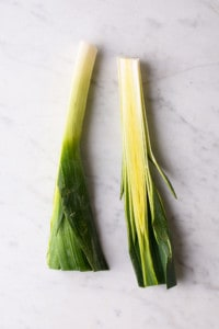 A leek sliced in half lengthwise, on a marble table
