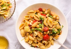 Summer pasta salad with tomatoes, artichokes, chickpeas, and arugula in a white bowl on a white tablecloth