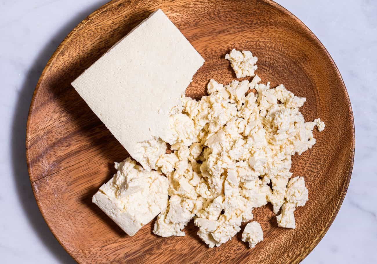 A complete tofu guide: Extra-firm uncooked tofu crumbled on a wooden plate