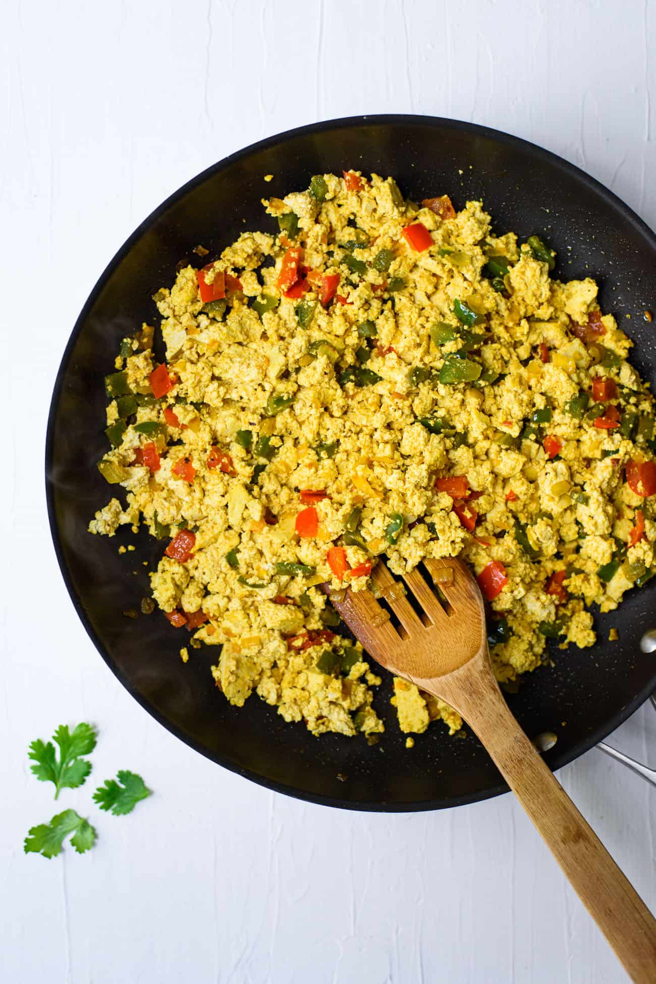 Scrambled tofu with turmeric, onions, and peppers in a non-stick skillet