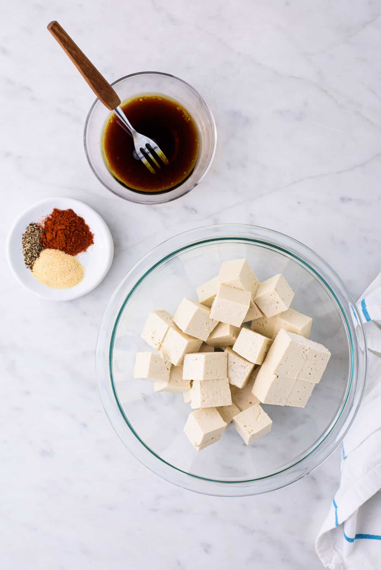 Cubed tofu in a Pyrex bowl next to soy sauce and spices