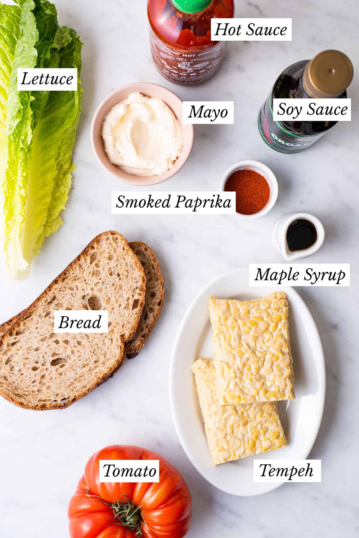 Ingredients gathered to make vegan BLT sandwiches: tempeh 'bacon', sourdough bread, lettuce, sliced tomatoes, and spicy mayo.