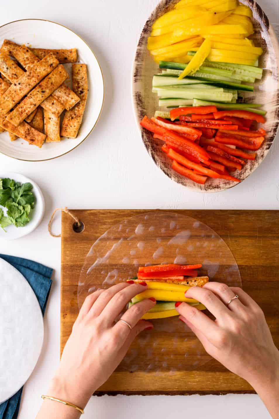 Woman's hands rolling a Vietnamese summer roll on a wooden board, alongside sliced vegetables and seared tofu