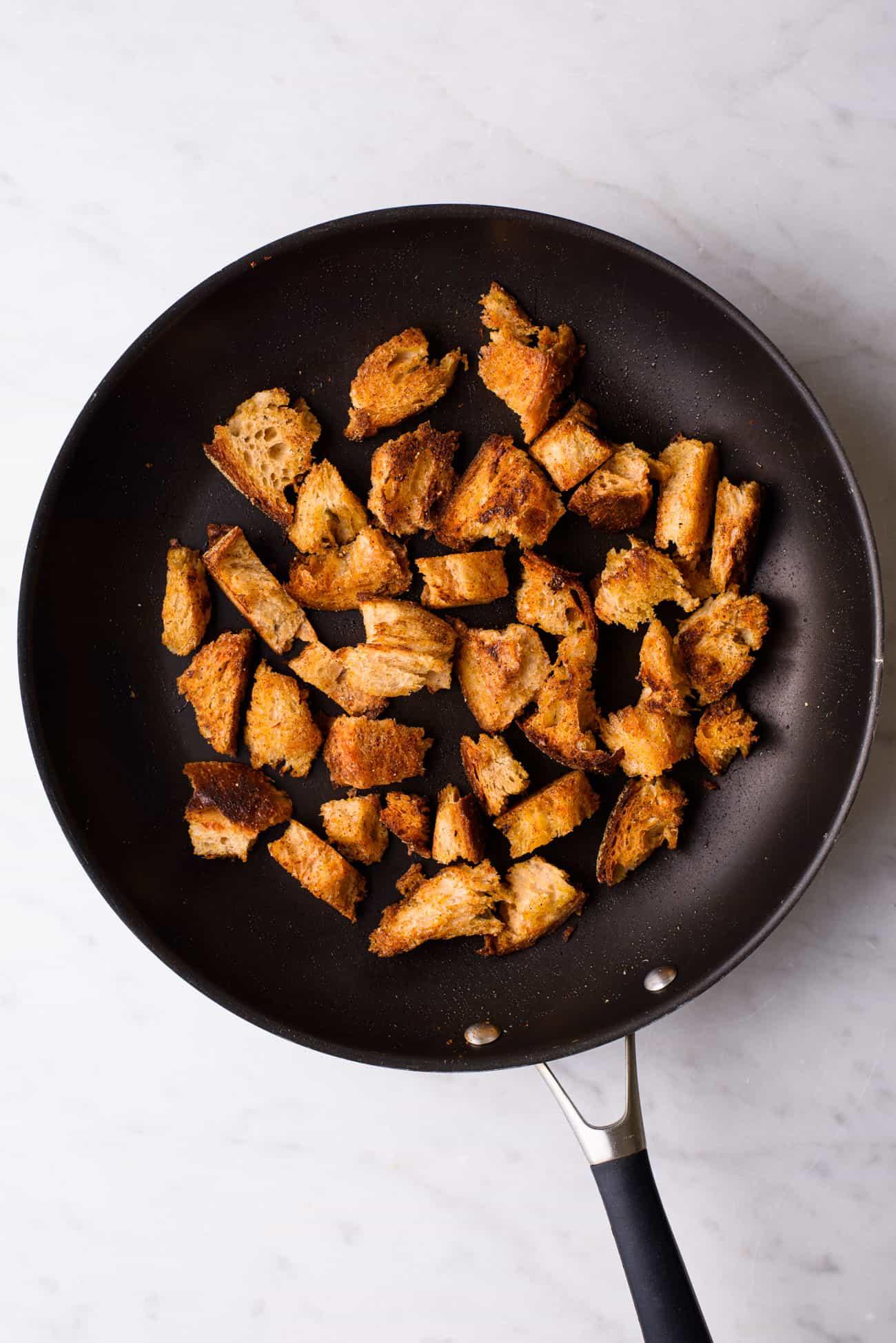 Crispy croutons in a black skillet