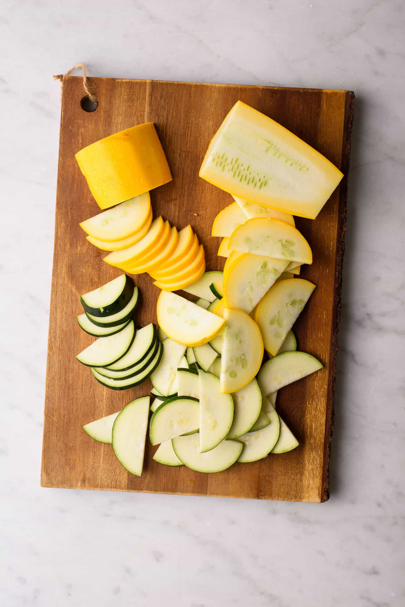 Zucchini and yellow summer squash sliced into half-moons on a wooden board