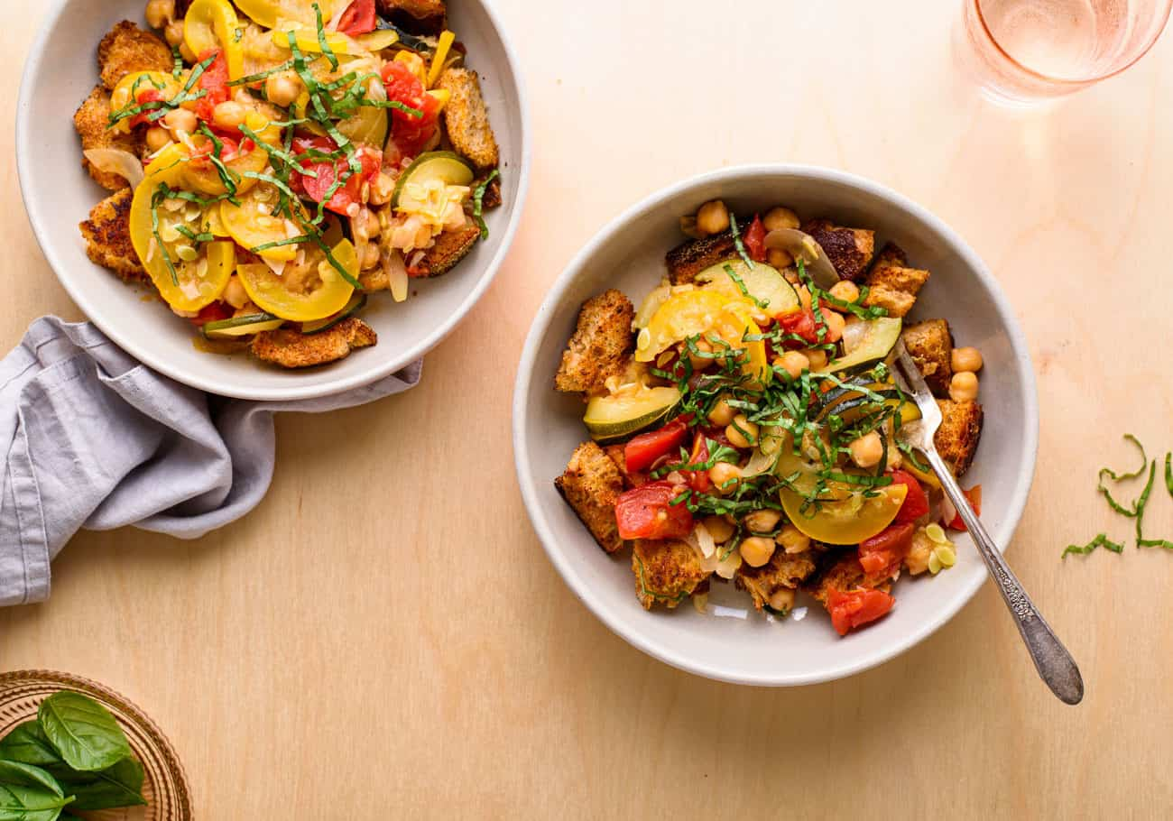 Two bowls of warm panzanella salad on a wooden table