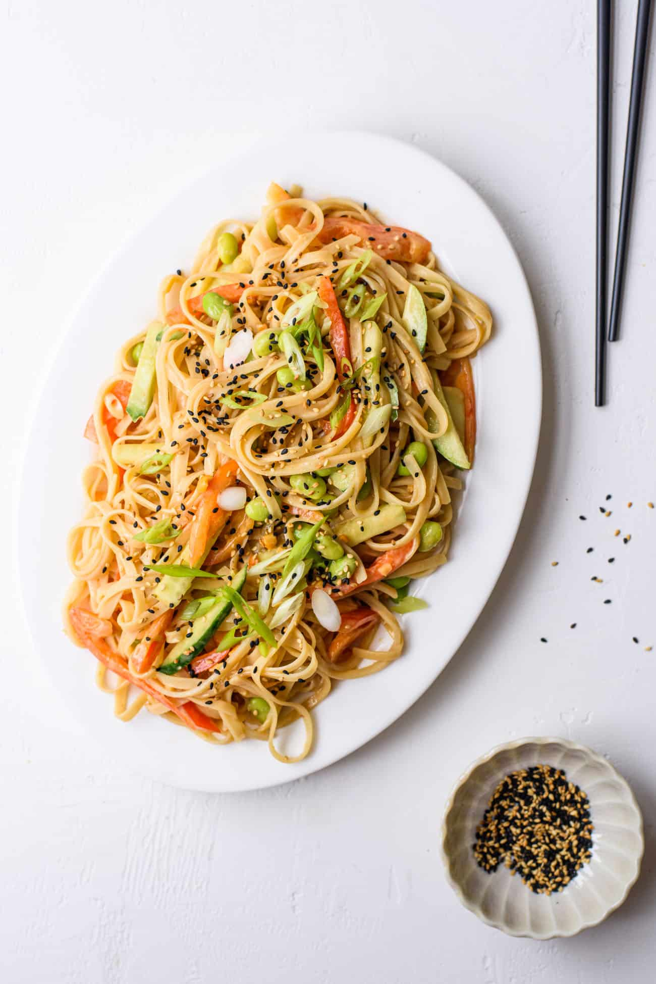 Cold peanut noodle salad with cucumbers, bell peppers, and edamame on a white oval platter on a white table next to chopsticks