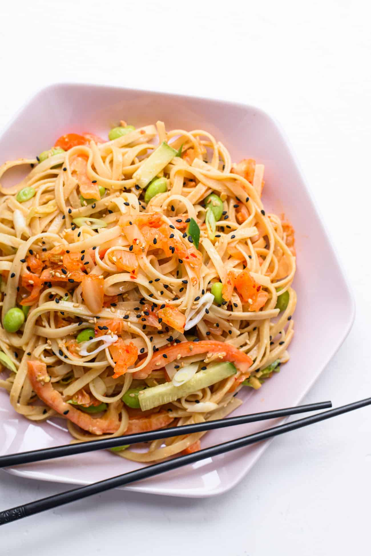Cold peanut noodle salad with kimchi on a pink hexagonal plate with black chopsticks