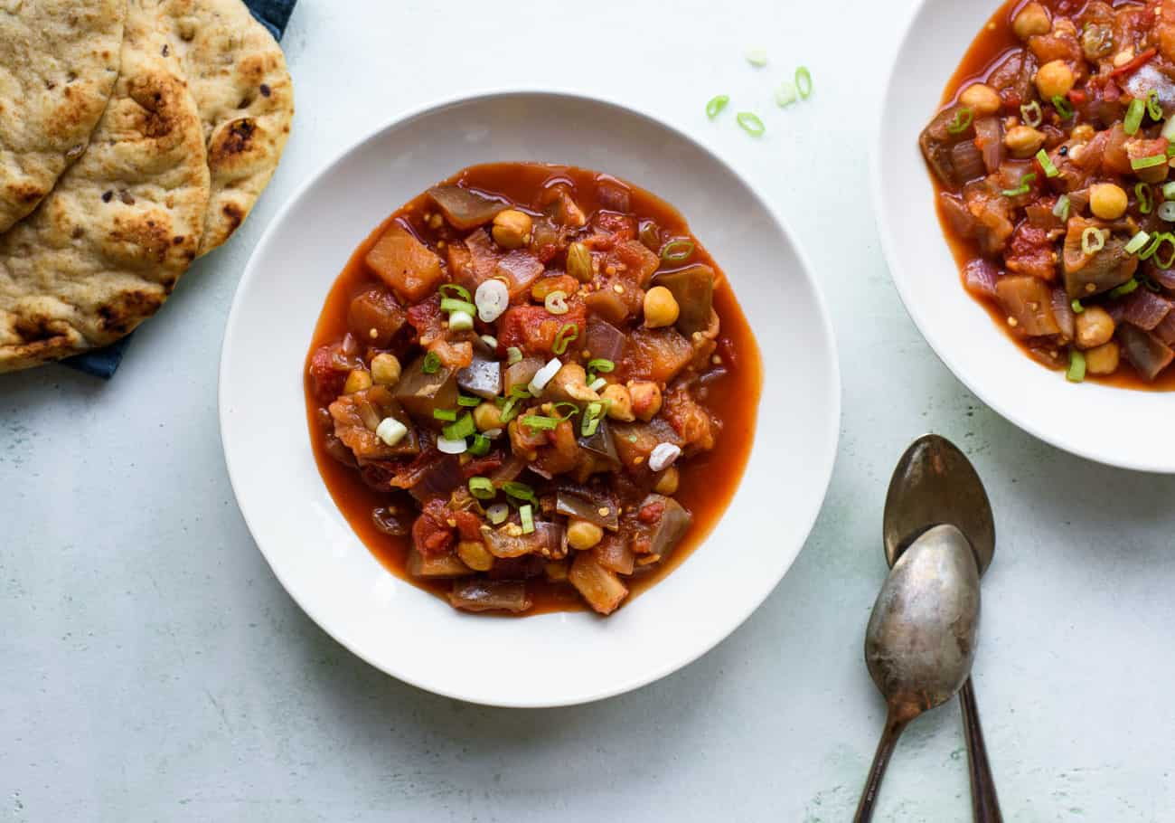 Two white bowls of eggplant chickpea stew next to a pile of flatbreads