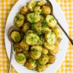 Ukrainian dill potatoes on a white oval platter on a yellow gingham tablecloth