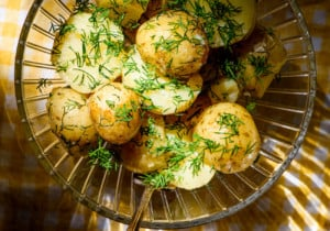 Ukrainian dill potatoes in a glass bowl on a yellow gingham tablecloth