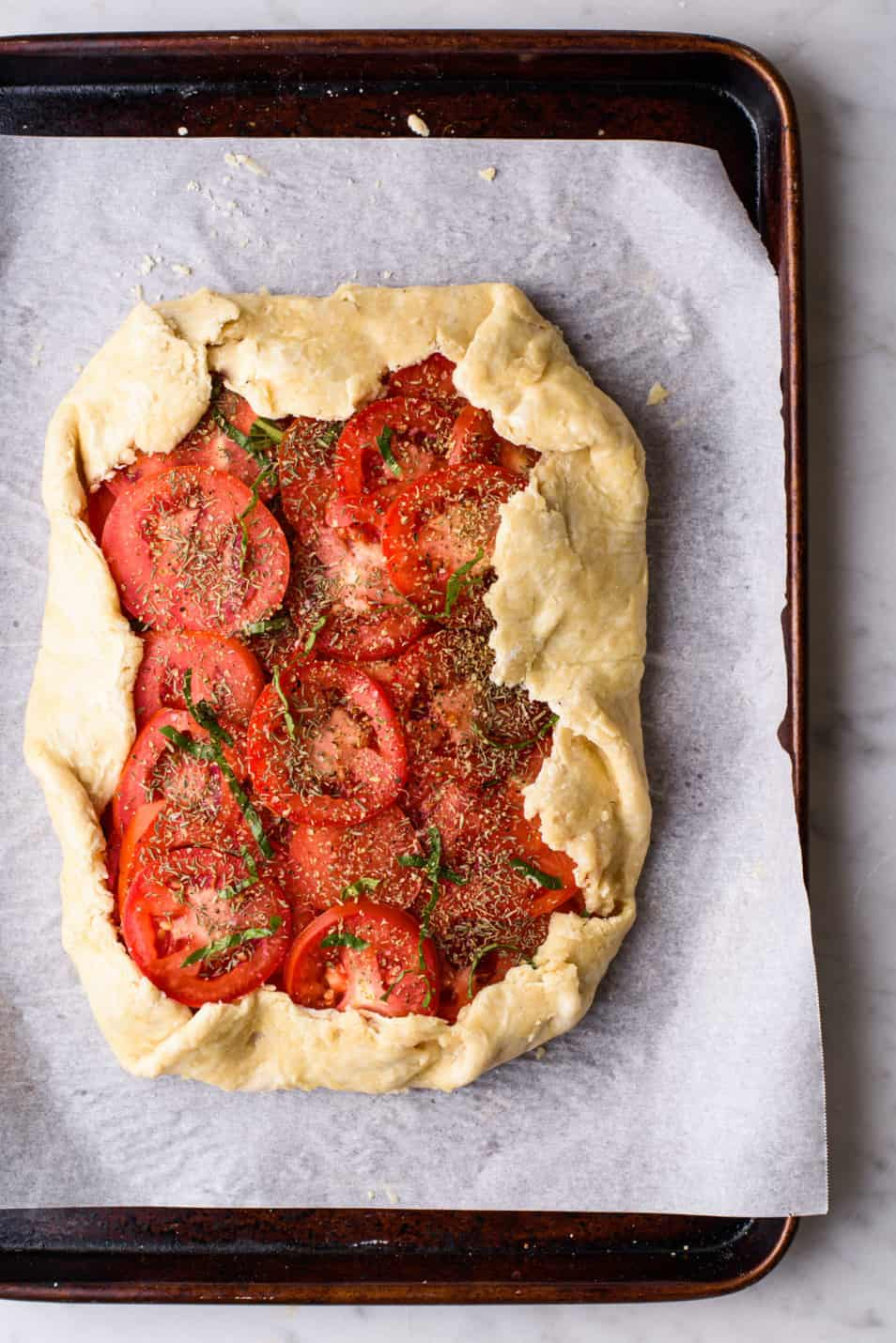 A raw tomato galette on a baking sheet, ready for the oven