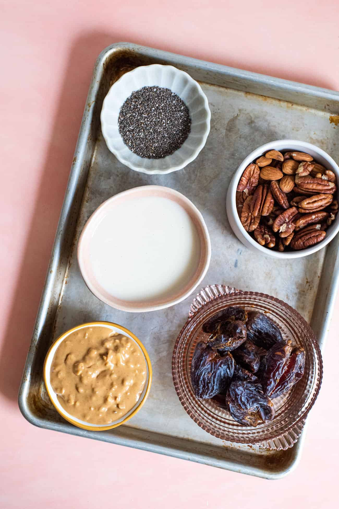 Chia seeds, coconut butter, peanut butter, almonds, and dates arranged on a small baking sheet