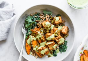 A bowl of farro, tofu, sweet potatoes, and kale with cilantro tahini dressing on a marble table