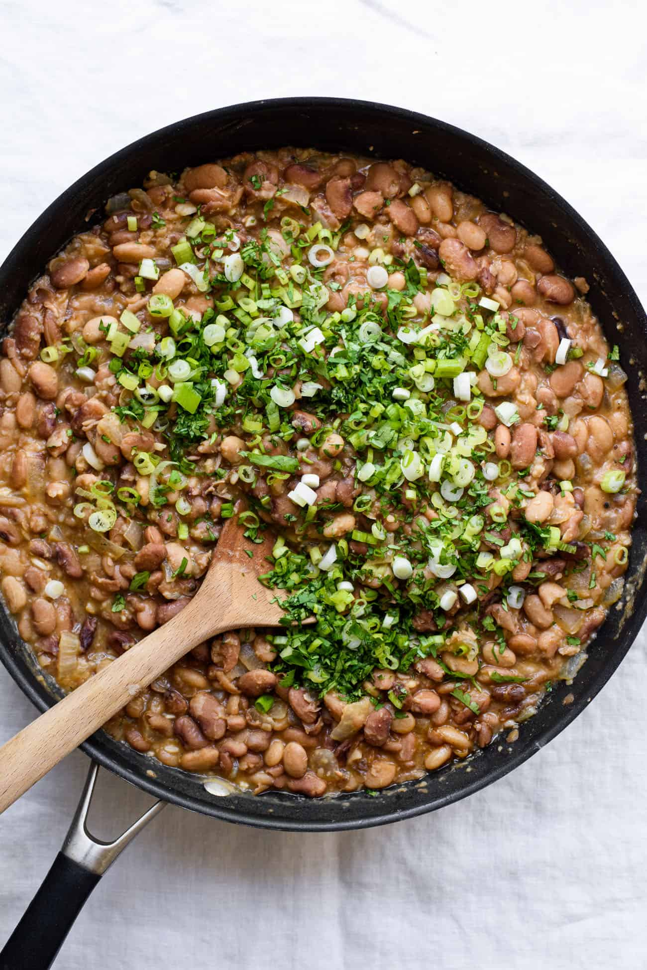Brothy, refried pinto beans with a heap of cilantro and scallions on top