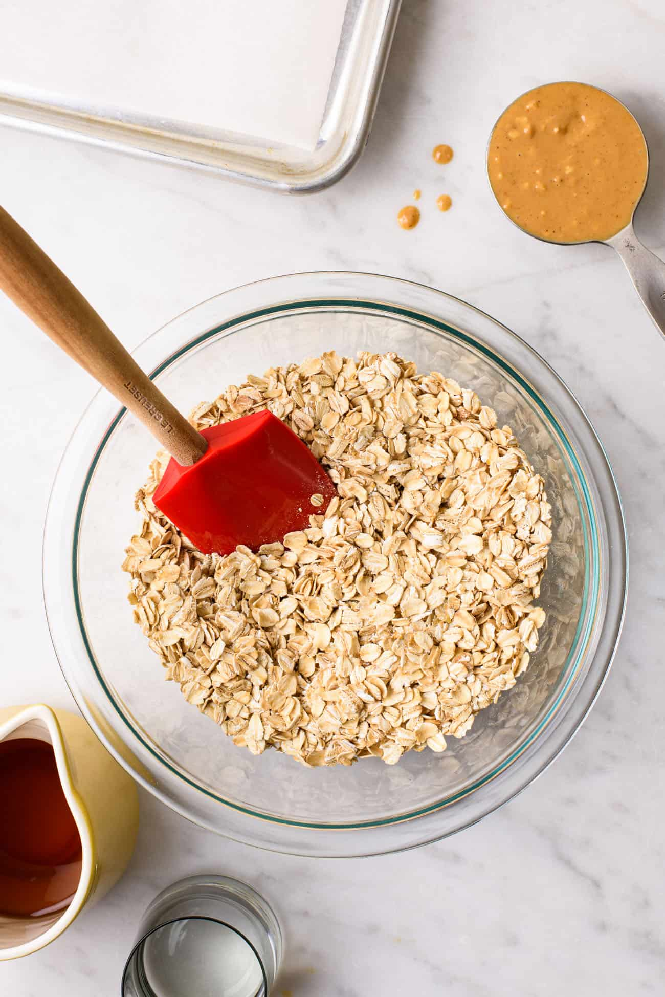 A Pyrex bowl with rolled oats next to a measuring cup with peanut butter